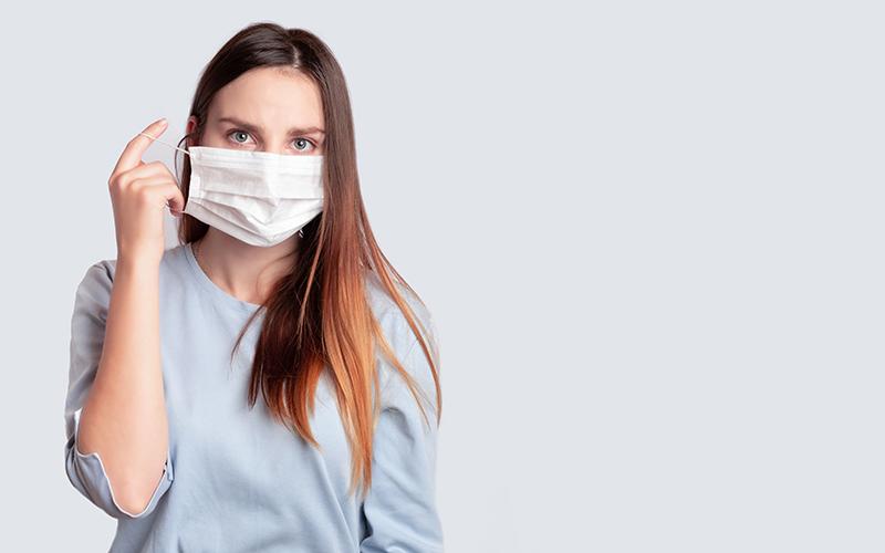 Mulher usando máscara de proteção contra o Coronavírus.