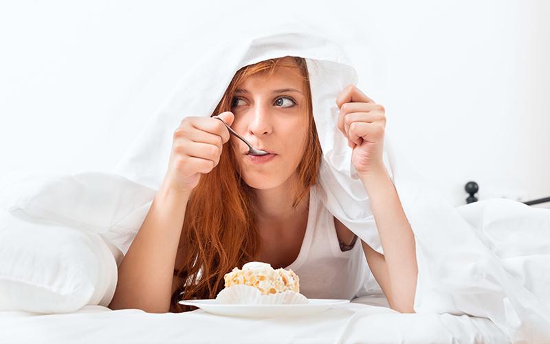Mulher comendo doce embaixo das cobertas