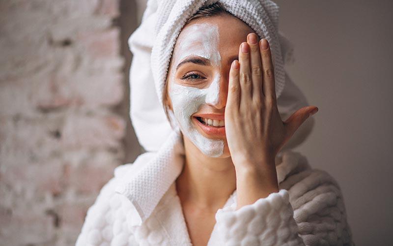 em fundo cinza, centralizada no meio da imagem, está uma mulher usado um roupão branco e uma toalha branca enrolada nos cabelos. A mulher tem olhos claros, é branca e está sorrindo. Com a mão esquerda ela cobre o lado esquerdo do rosto e no lado há um creme aplicado no rosto.